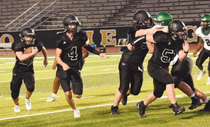 JV RB Caleb Dean bursts out of the backfield as #4 Ricky Gall, #50 Brooklyn Freeman, and #51 Jesse Meyers get out front to block.