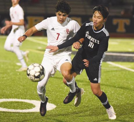 Pirate Ryan Liu battles a Bridge City Cardinal for control of the ball in Friday's game.