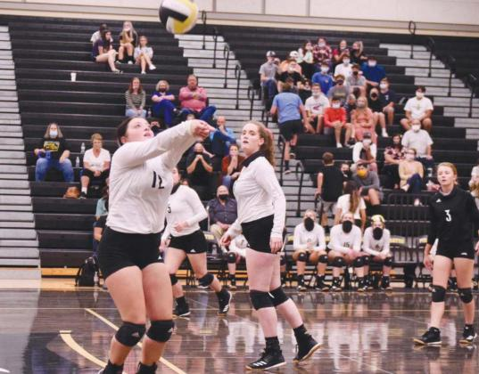 Claire Villadsen, foreground, sets the ball for Rylee Sherman, center.